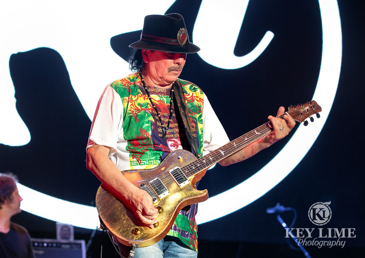 Carlos Santana with gold PRS guitar, surprise appearance at Rob Thomas concert, green and white shirt event photography