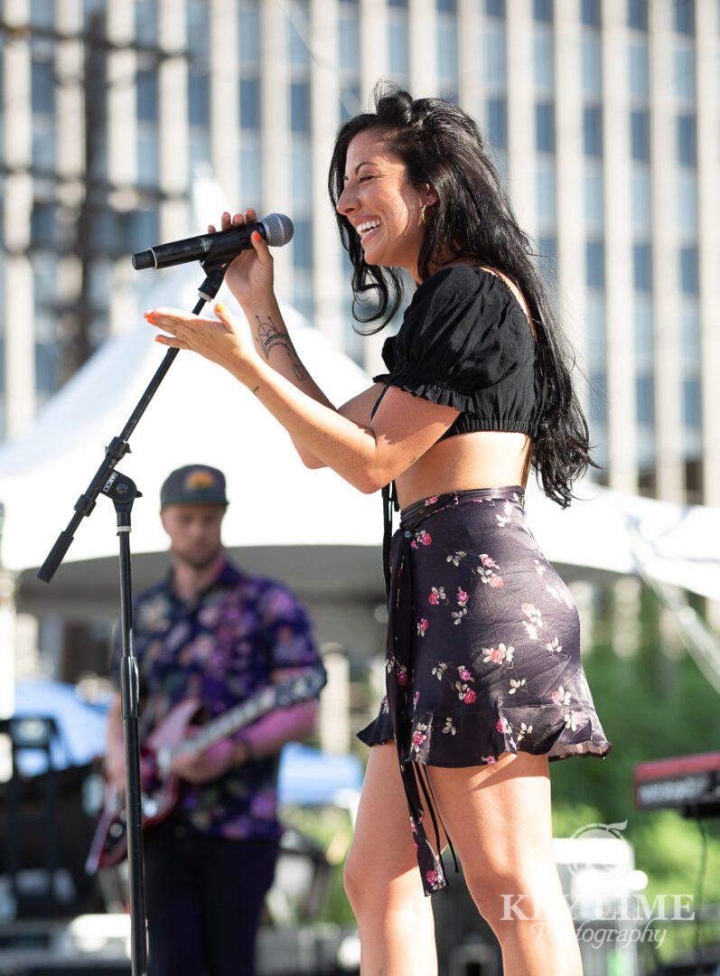 Delacey singing, long black hair, black crop top and floral skirt
