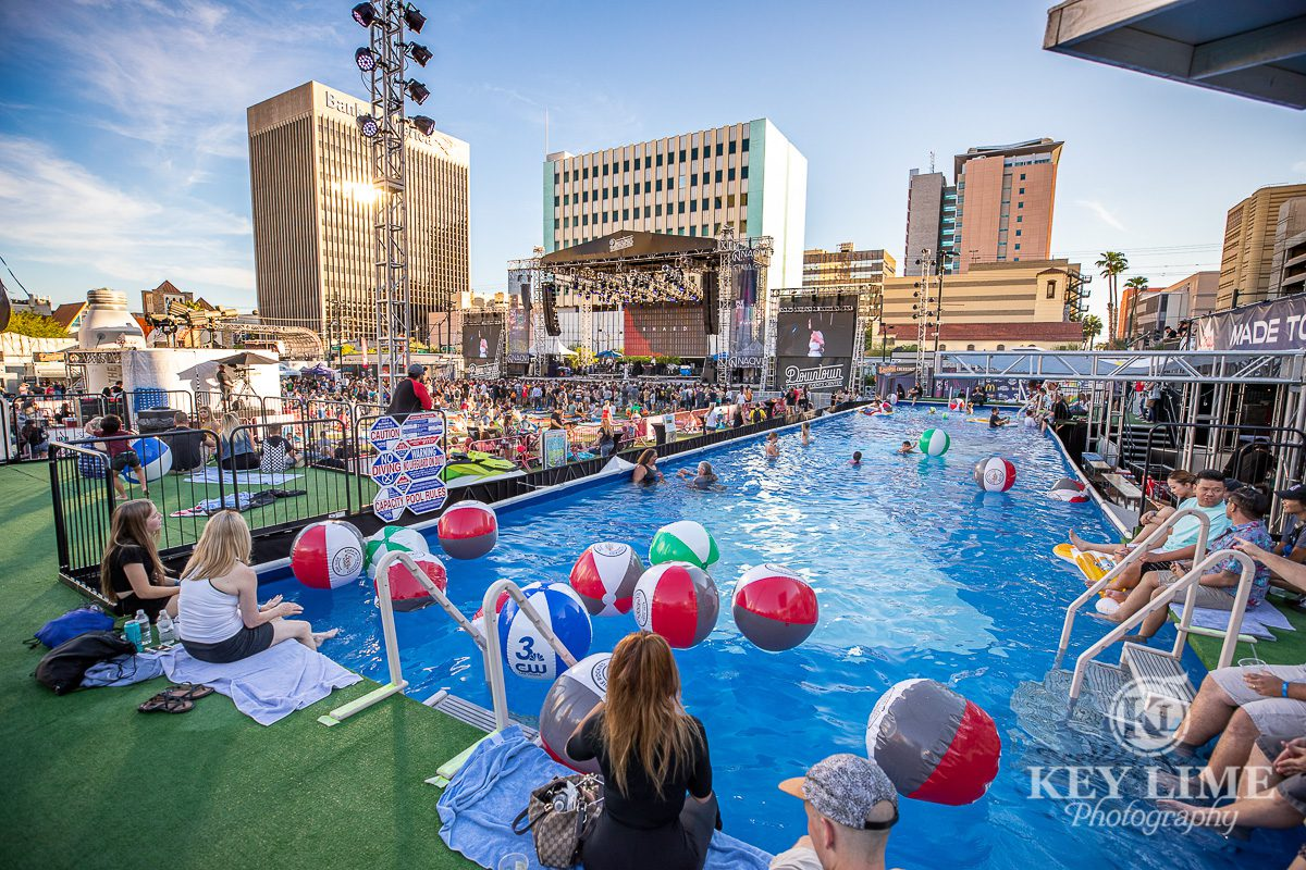 Event photography of the pool view and VIP cabanas area at Bite of Las Vegas 2019, Blue water with red and white beach balls. Girls sitting on the pool edge with the downtown Vegas city skyline in the near distance.
