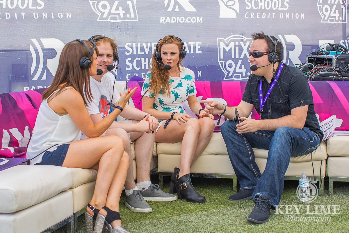 The Rua interviewed by Shawn Tempesta during Bite of Las Vegas. Three band members sitting on a white couch, being interviewed by Shawn. All four people are wearing headset microphones.
