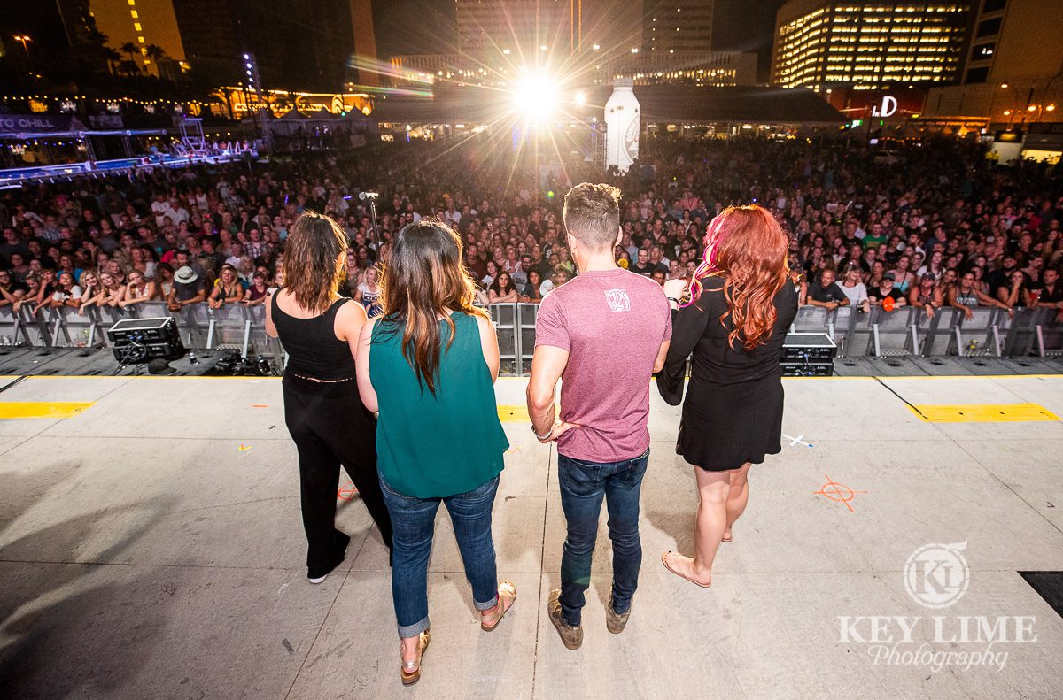 Radio DJs onstage. Point of view from the stage looking over DJ's shoulders at an ocean of people. Sold out event center during Bite of Las Vegas 2019
