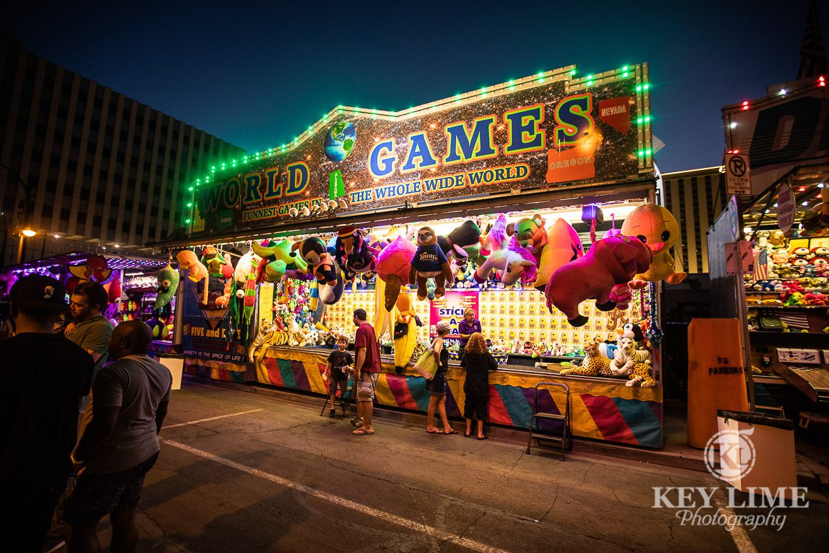 Photo of carnival games at Bite of Las Vegas 2019. Vivid pink and green colors with flashy bulbs and stuffed animals.