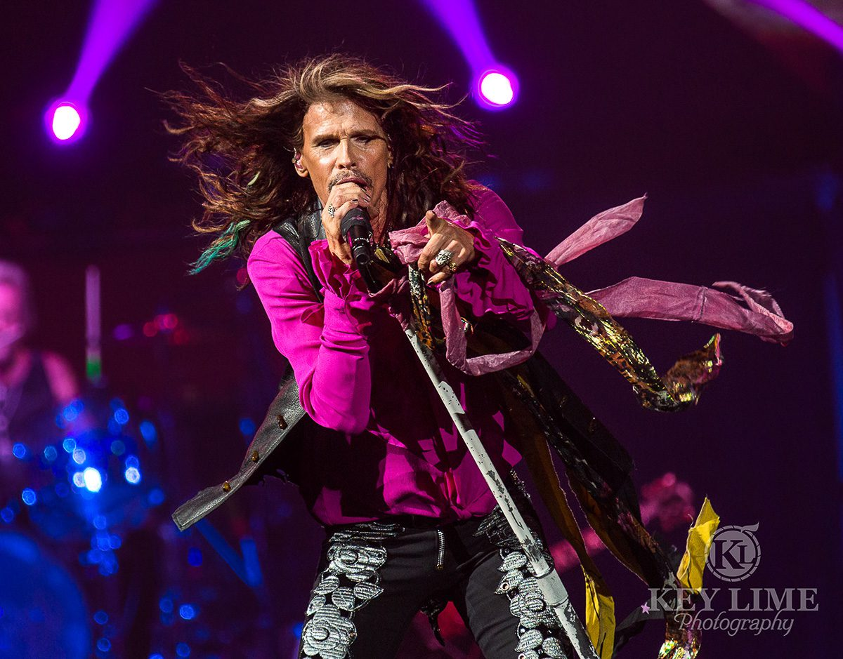 Iconic event photographer image of Steven Tyler during an Aerosmith performance. Tight, black embellished jeans with a silky magenta shirt and black vest.