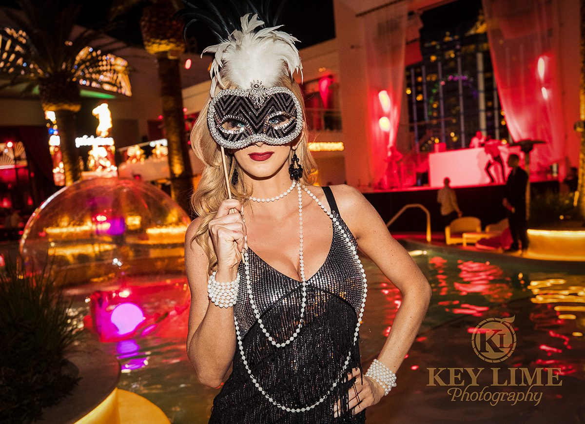 Corporate masquerade event in Las Vegas. Blonde woman with red lipstick, holding a mask over her eyes. Party photographer image at nightclub pool.