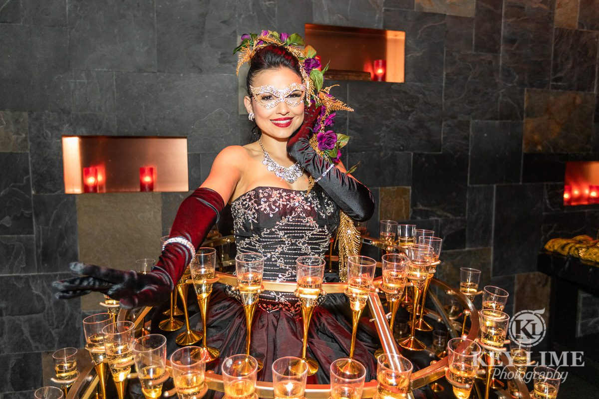 Las Vegas photographer image of model smiling while supporting a dress that serves champagne flutes during an event.