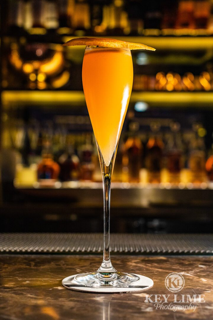 Cocktail image. Orange drink in Grappa Glass.