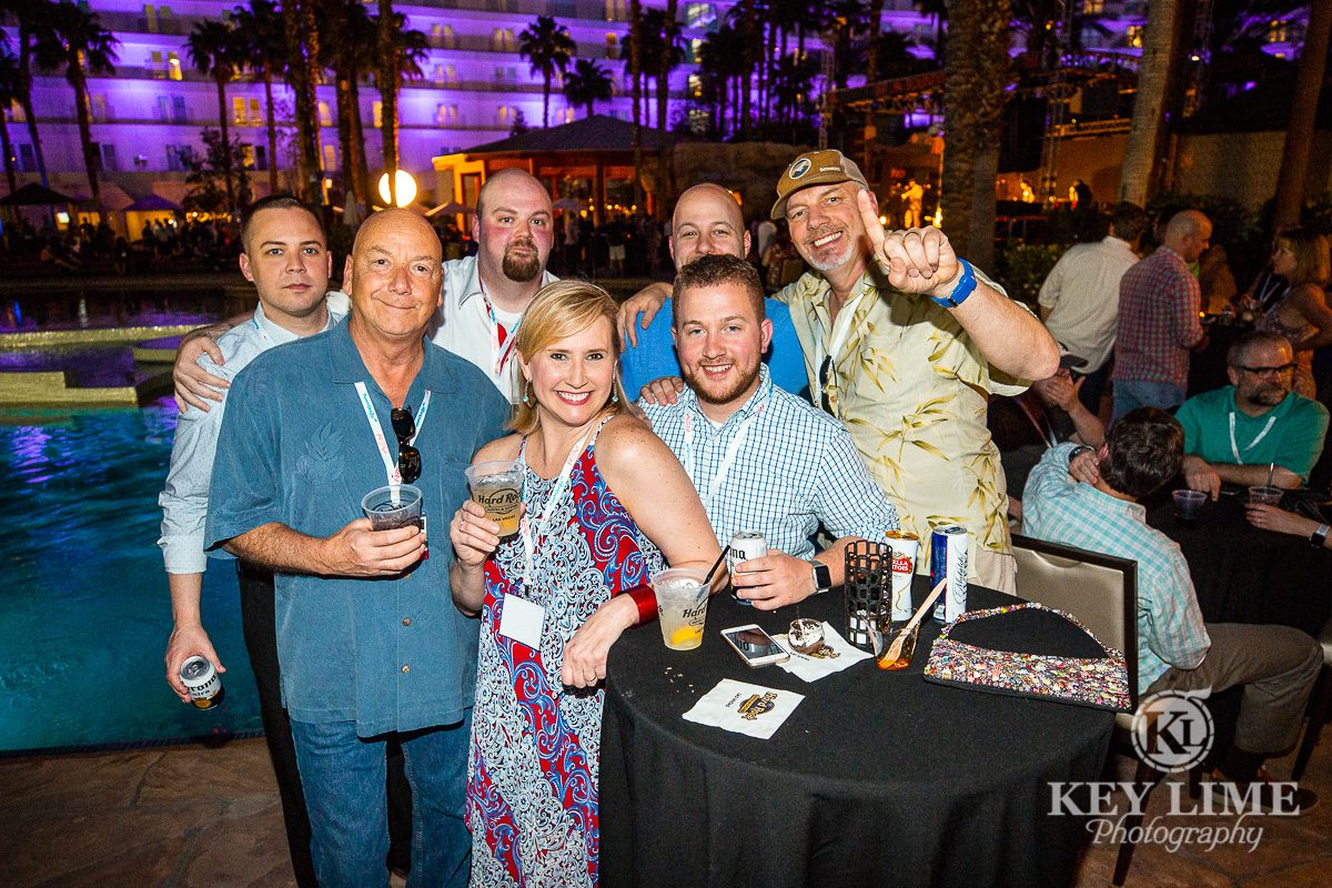 Company party near Las Vegas resort pool. Event photographer image of smiling, jovial coworkers.