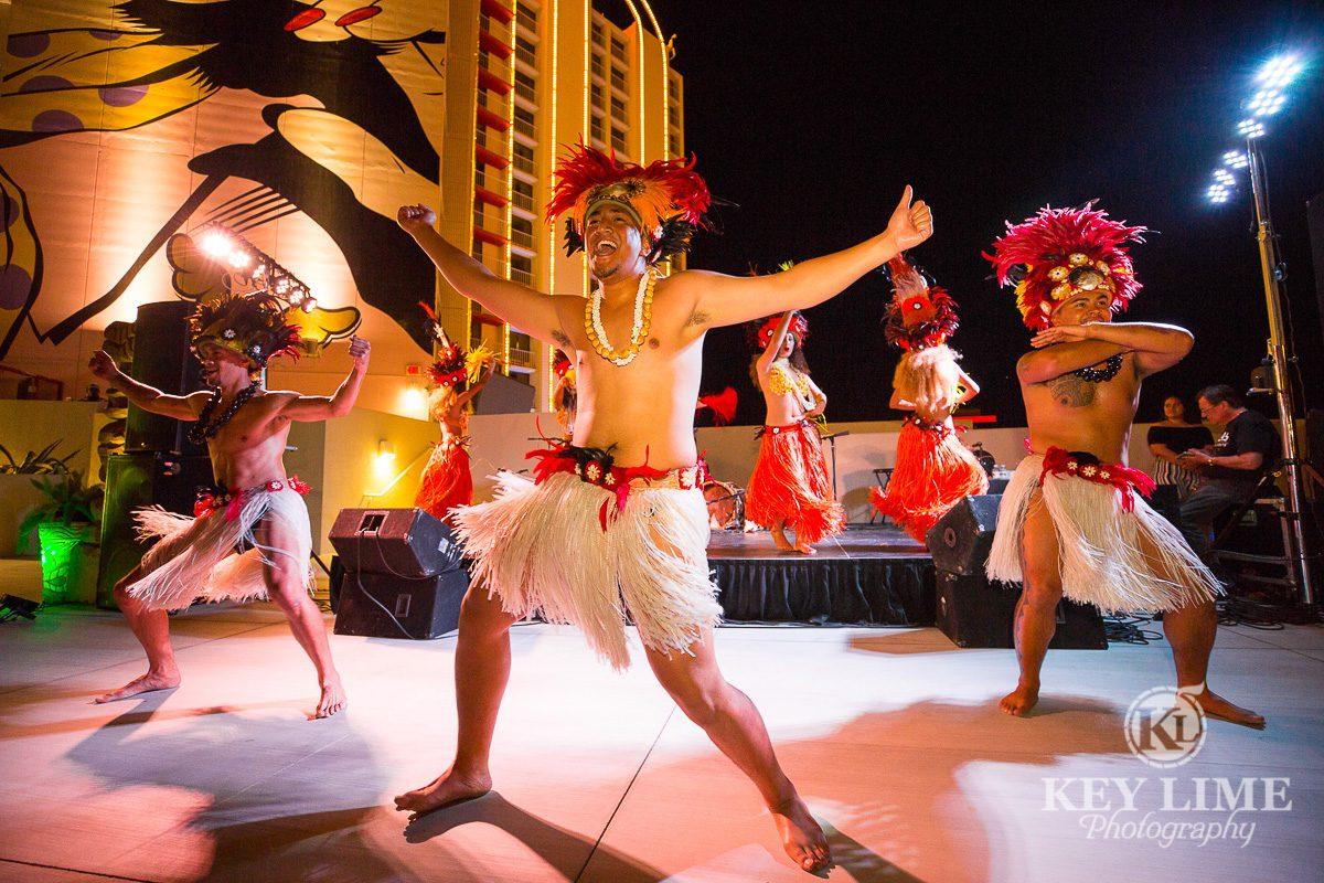 Rooftop luau party. Smiling male hula dancers aka Warrior dancers.