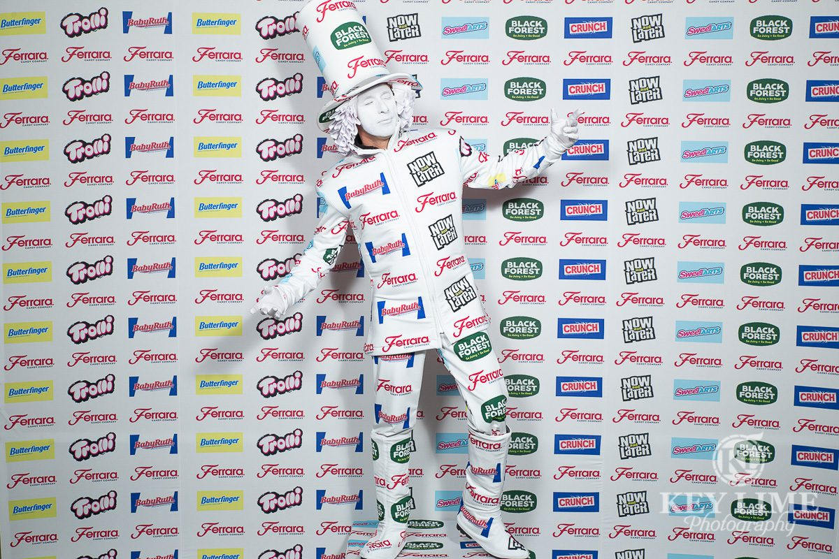 Step and repeat event photographer image. Performer wearing logo suit to blend in with step and repeat.