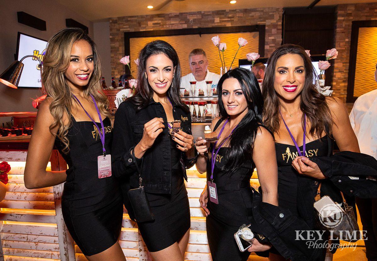 Attractive models sampling amuse-bouche at a Las Vegas culinary event