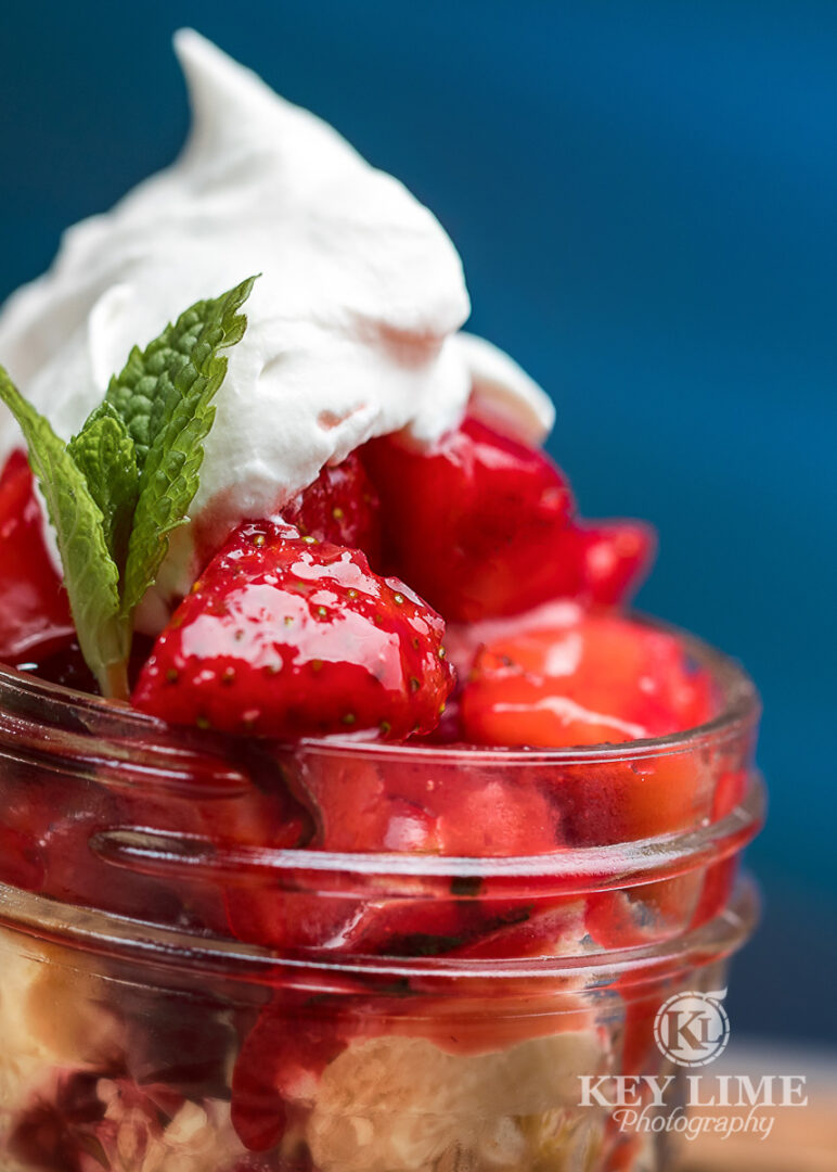 Alluring strawberry dessert photo. Whip cream and shortcake on a blue background.