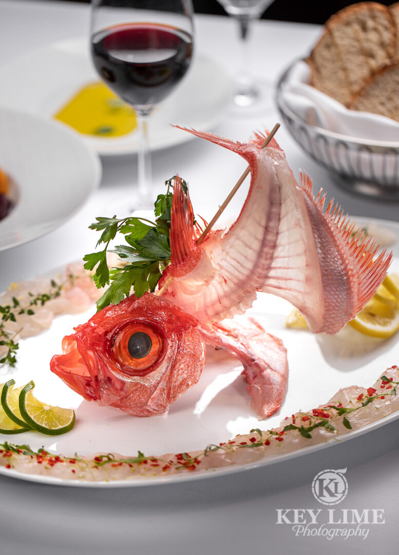 Classy food photography of seafood plate. Fish bite line the rim of the plate. Fish head with spine and tail have been displayed elegantly as the centerpiece. Food stylist added relevant props and additional plates.
