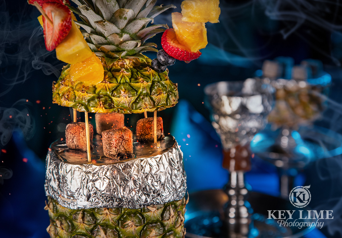 Pineapple hookah with fruit skewers. Picture uses long exposure to show coals glowing hot.