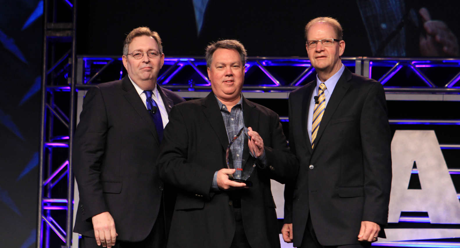 three men in suits holding a glass award for safety