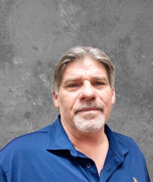 man with gray hair and beard in dark blue shirt