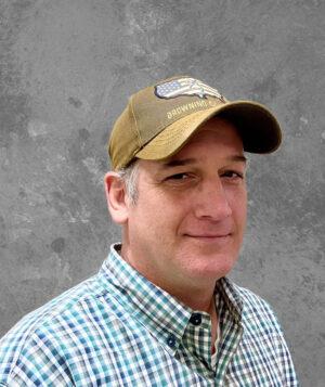 man in plaid shirt and ball cap