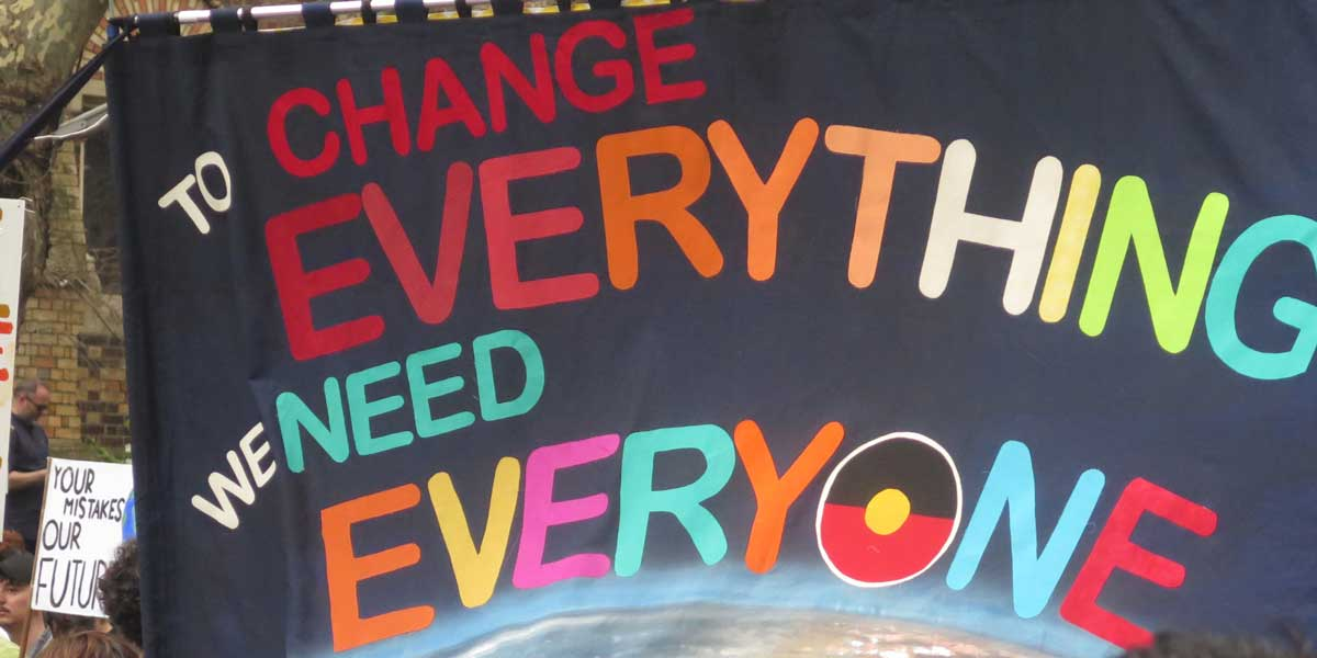 """Sign reading """"to change everything we need everyone"""""""