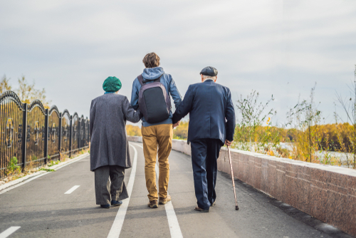 Young man walking with older couple shutterstock_1233617758