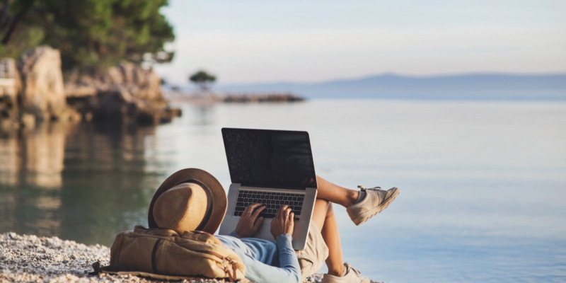 Woman reclines on beach with head on duffle bag and laptop on lap with legs crossed overlooking a body of water