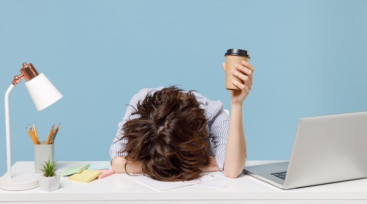 Woman holding coffee cup has her head down on her desk between a laptop and desk lamp