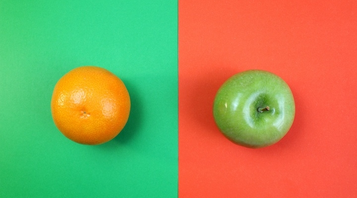 An orange (the fruit) sits on a green background, while a green apple sits against a red-orange background