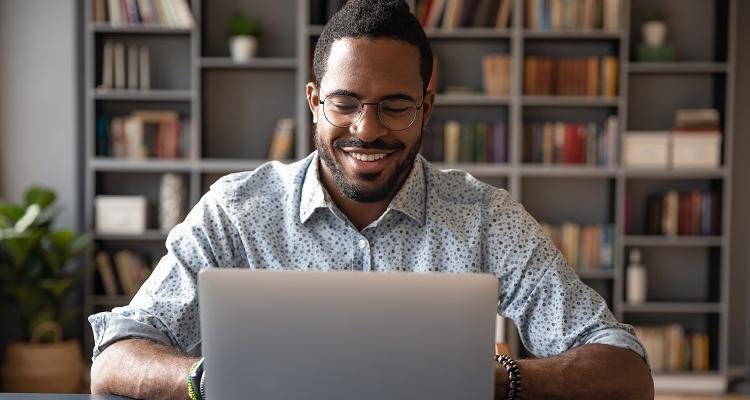 Man sits at his laptop, typing and smiling at his screen.