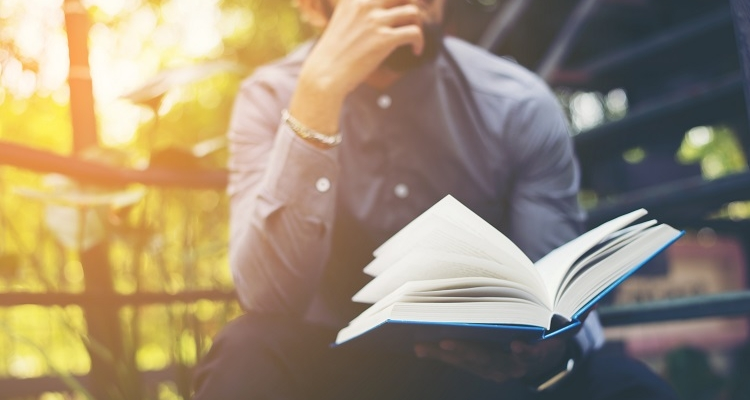 Man with an open book looking pensive as he reads outdoors