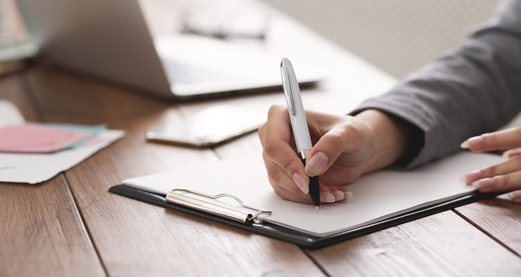 Hand holding pen, filling out a W-9 form on a clipboard with laptop in background
