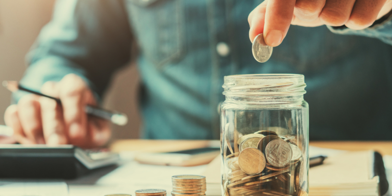 Hand placing a quarter into a jar of quarters