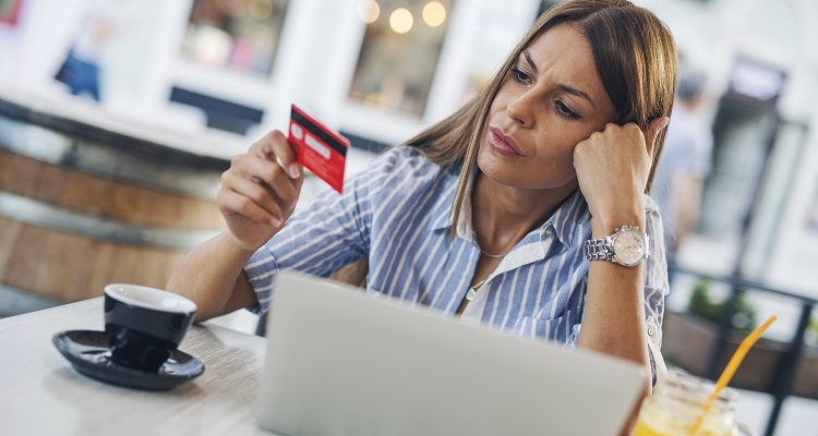 Woman looking worried and confused as she contemplates a credit card in front of her laptop.