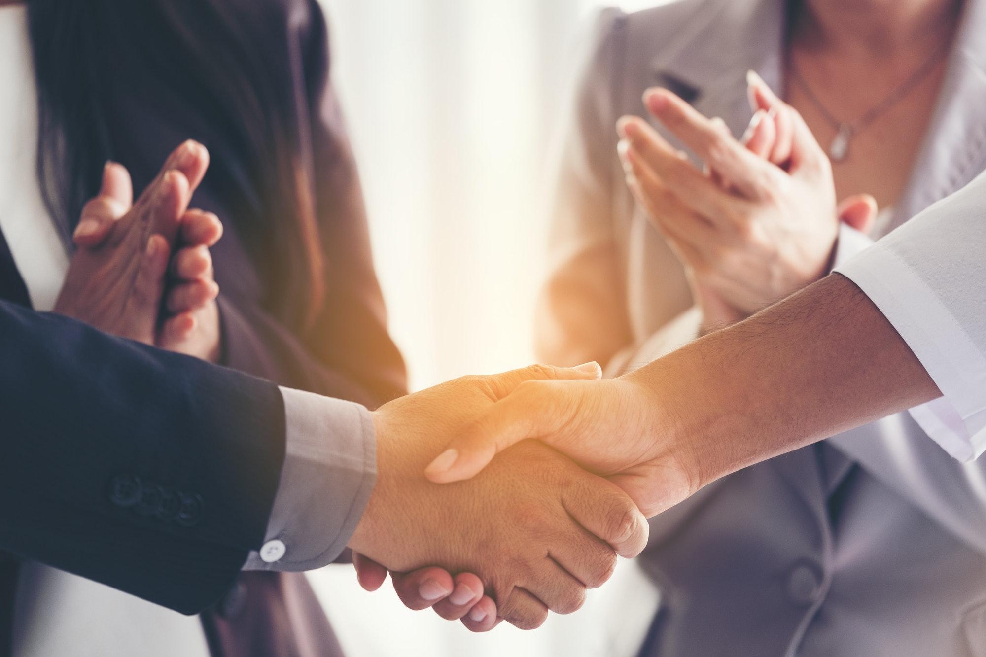 Businessmen making handshake in the city - business etiquette