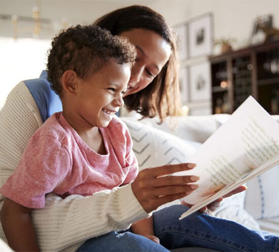 Black mother reading a book to her Black daughter