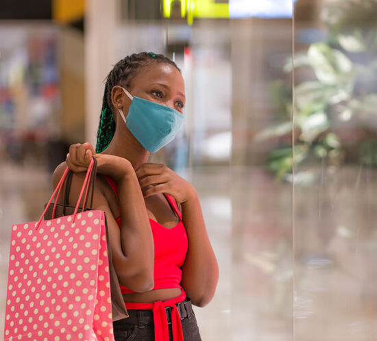 Retailers and mask policies, article by Celia Schnupp of Perez Morris, young woman shopping for clothes with a mask