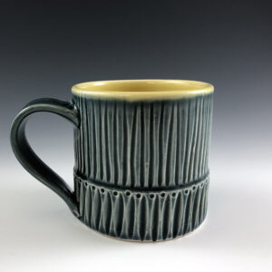 Carved porcelain mug by Dyann Myers. Wheel-thrown with glossy blue glaze.