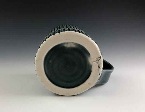 Carved porcelain mug by Dyann Myers. Wheel-thrown with glossy blue glaze.