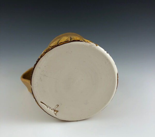 Carved porcelain mug by Dyann Myers. Wheel-thrown with matte gold glaze.