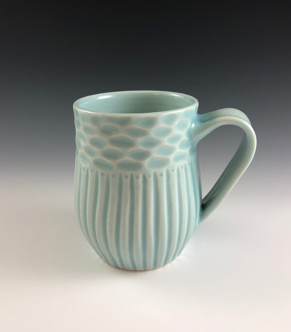 Carved porcelain mug by Dyann Myers. Wheel-thrown with glossy light blue glaze.
