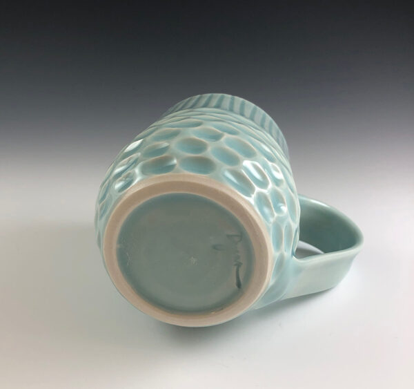 Carved porcelain mug by Dyann Myers. Wheel-thrown with glossy light blue glaze.