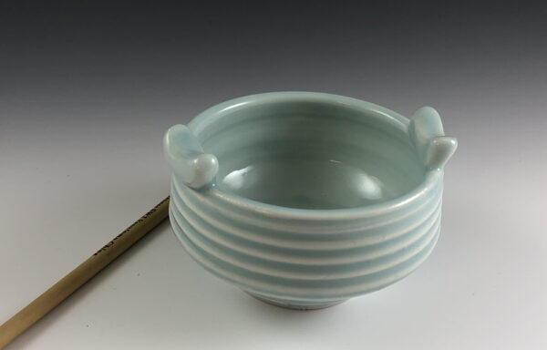 Carved porcelain brush bowl by Dyann Myers. Wheel-thrown with glossy light blue glaze.