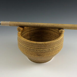 Carved porcelain brush bowl by Dyann Myers. Wheel-thrown with matte gold glaze.