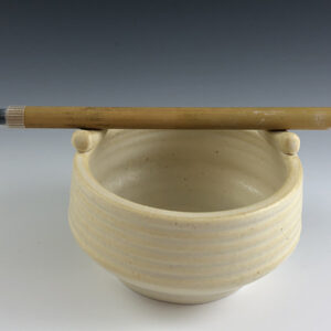 Carved porcelain brush bowl by Dyann Myers. Wheel-thrown with matte white glaze.