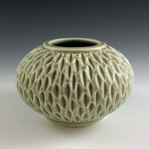 Carved porcelain vase by Dyann Myers. Small wheel-thrown with matte green glaze.