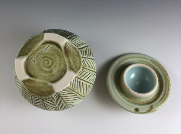 Carved porcelain jar by Dyann Myers. Small wheel-thrown with matte green glaze.