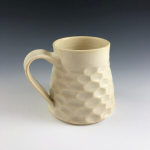 Carved porcelain mug by Dyann Myers. Wheel-thrown with matte white glaze.