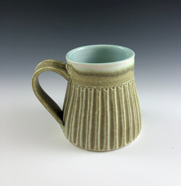 Carved porcelain mug by Dyann Myers. Wheel-thrown with matte green glaze.