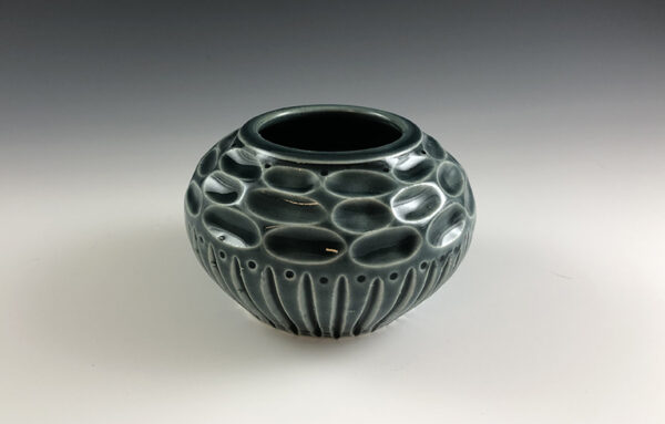 Carved porcelain vase by Dyann Myers. Small wheel-thrown with glossy blue glaze.