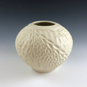 Carved porcelain vase by Dyann Myers. Wheel-thrown glazed in white sands glaze.
