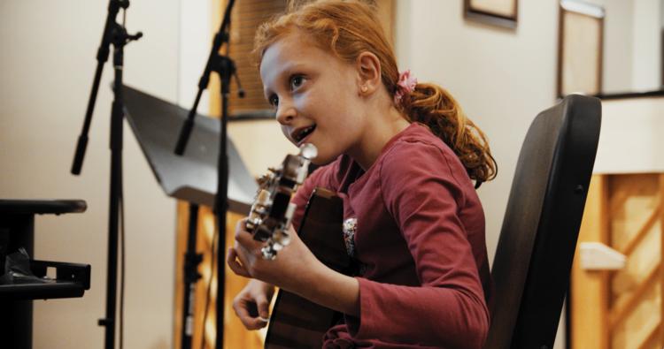 Young girl plays guitar