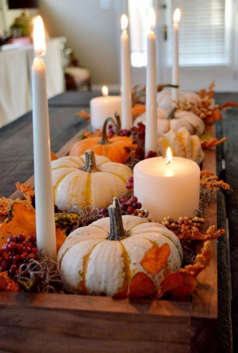 White candles with mini pumpkins and gourds