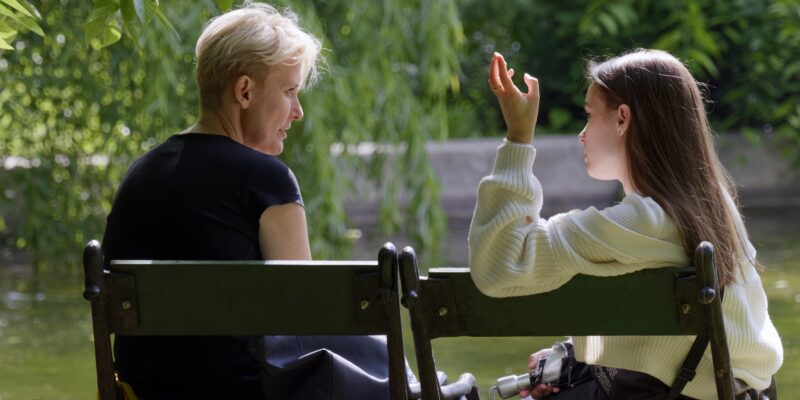Girl sitting with her mother on a bench talking about overstepping boundaries.